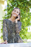 Beautiful young brunette woman calling by phone. Summer park outdoors Royalty Free Stock Image