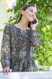 Beautiful young brunette woman calling by phone. Summer park outdoors Stock Photos