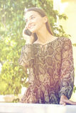 Beautiful young brunette woman calling by phone. Summer park outdoors Stock Photography