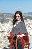Beautiful young brunette woman with camera in the hands above the city of Kavala,Greece. Woman photographer on the cityscape of Kavala,Greece royalty free stock image