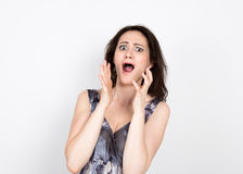 Beautiful young brunette woman in a colorful dress posing and expresses different emotions. great fear. close-up portret Stock Photo
