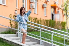 Beautiful young brunette woman in denim casual style standing on upstairs, holding coffee, excited, waving her hand and greeting royalty free stock images
