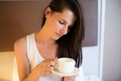 Beautiful young brunette woman drink coffee in the morning, on w. Hite bed Royalty Free Stock Photography