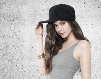 Beautiful young woman in fullcap on grey background. Beautiful young brunette woman in fullcap on grey background. R&B style royalty free stock photos