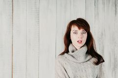 A pretty long haired girl in a gray pullover, surprised big eyes. A beautiful young brunette woman in a gray pullover, surprised big eyes, open mouth, with light Royalty Free Stock Photo