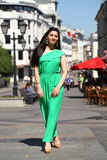 Beautiful young brunette woman in green long dress. Young beautiful brunette woman in a long green dress walking on the summer street Stock Image