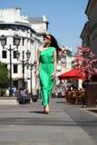 Beautiful young brunette woman in green long dress Stock Image