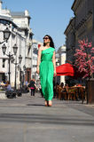 Beautiful young brunette woman in green long dress. Young beautiful brunette woman in a long green dress walking on the summer street Royalty Free Stock Image