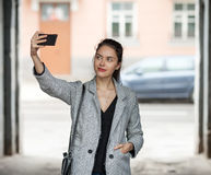 Beautiful young brunette woman in grey coat taking a selfie with her smartphone on city street cloudy day Stock Photography