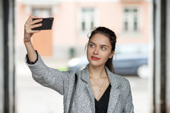Beautiful young brunette woman in grey coat taking a selfie with her smartphone on city street cloudy day Royalty Free Stock Images