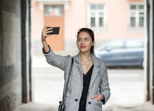 Beautiful young brunette woman in grey coat taking a selfie with her smartphone on city street cloudy day Stock Photo
