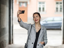 Beautiful young brunette woman in grey coat taking a selfie with her smartphone on city street cloudy day Royalty Free Stock Photography