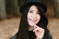 Beautiful young brunette woman in a hat holding a red straw. Stock Images