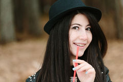 Beautiful young brunette woman in a hat holding a red straw. Royalty Free Stock Photo
