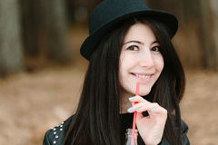Beautiful young brunette woman in a hat holding a red straw. Stock Photography