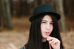 Beautiful young brunette woman in a hat holding a red straw. Royalty Free Stock Photography
