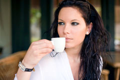 Beautiful young brunette woman having coffee. Stock Image