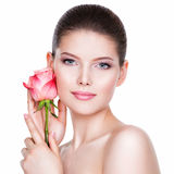 Beautiful young brunette woman with healthy skin. Beautiful young brunette woman with healthy skin and pink flowers near face - isolated on white royalty free stock photos