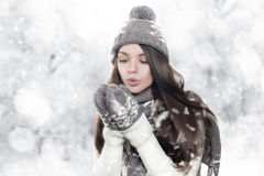 Beautiful young brunette woman heating hands. On winter background royalty free stock images