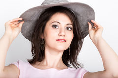Beautiful young brunette woman holding a broad-brimmed hat, she hides her face behind a hat. girl flirting concept. Expression of different emotions Royalty Free Stock Photography