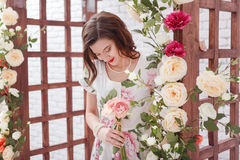 Beautiful young brunette woman with long curly hair is posing around arch with flowers. Beautiful young brunette woman with long curly hair is posing around Royalty Free Stock Images