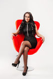 Beautiful young brunette woman with long hair in a black dress sitting on chair  white background Royalty Free Stock Photo