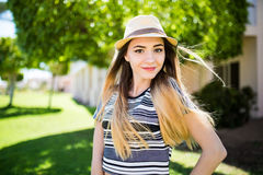Beautiful young brunette woman with long hair flying in the wind and brown hat in park in summer. Royalty Free Stock Images