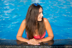 Beautiful young brunette woman with long hair in pink bikini kee. Ps his hands on the edge a pool in the summer Stock Photography
