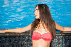 Beautiful young brunette woman with long hair in pink bikini kee. Ps his hands on the edge a pool in the summer Stock Photos