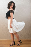 Beautiful young brunette woman looking at her white skirt Stock Photography