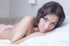Beautiful young brunette woman lying on bed Stock Photos