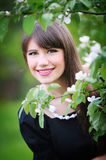 Beautiful young brunette woman on the meadow with white flowers Stock Photography