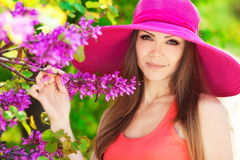 Beautiful young brunette woman on the meadow with white flowers on a warm summer day. Close portrait of pretty cheerful woman wearing white dress and straw pink stock photography