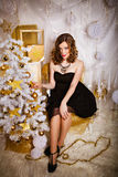 Beautiful young brunette woman near Christmas tree Stock Images