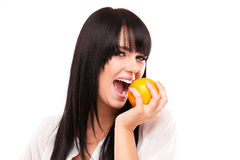 Beautiful young brunette woman with orange on white background Stock Photography
