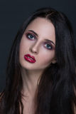 Beautiful young brunette woman with perfect skin. Closeup portrait on dark grey background. Wavy hairstyle, bright luxury make-up, red lips Royalty Free Stock Photography
