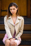 Beautiful young brunette woman in pink dress and gray jacket Stock Images