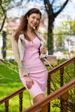 Beautiful young brunette woman in pink dress and gray jacket Royalty Free Stock Image