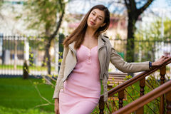 Beautiful young brunette woman in pink dress and gray jacket Stock Photos
