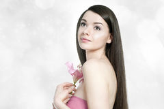 Beautiful young brunette woman with pink lilly. On grey background Stock Photo