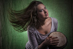 Beautiful sexy woman playing djembe drum Royalty Free Stock Photography