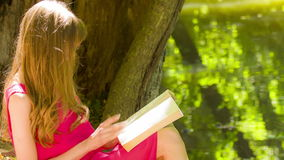 Beautiful young brunette woman reading a book stock footage