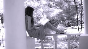Beautiful young brunette woman reading a book stock video