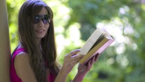 Beautiful young brunette woman reading a book stock video footage