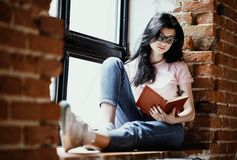 Free Beautiful Young Brunette Woman Reading Book Near Window At Home. Stock Photography - 106463062