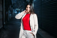 Beautiful young brunette woman in red blouse white coat evening outdoors royalty free stock images