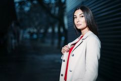 Beautiful young brunette woman in red blouse white coat evening outdoors. copy space royalty free stock image