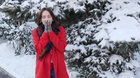 Beautiful young brunette woman in red coat, scarf, mittens,  smiling freezing trying to warm up, blowing on hands outside on winte. R snowy day stock video footage