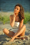 Beautiful young brunette woman relaxing on the beach Stock Photo