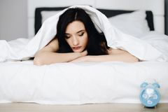 Beautiful young brunette woman relaxing and resting in bed royalty free stock photography